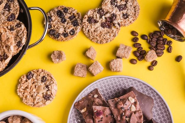 Cubos de açúcar sobrancelha; biscoitos de chocolate; grãos de café e placa de barras de chocolate em pano de fundo amarelo brilhante Foto gratuita