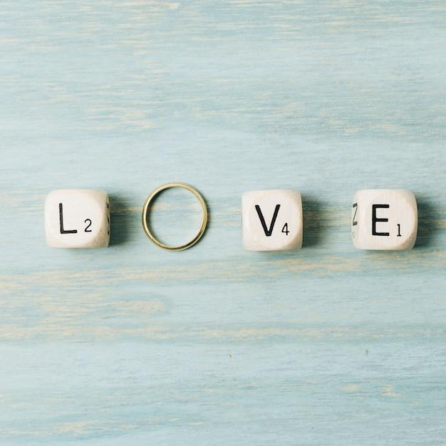 Cubos de carta de amor com anel de casamento de ouro no cenário de textura de madeira Foto gratuita
