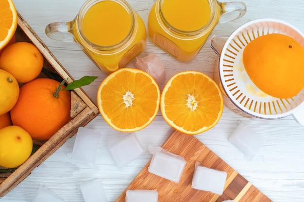 Cubos de gelo de vista superior na tábua de madeira na frente de copos de suco de laranja Foto gratuita