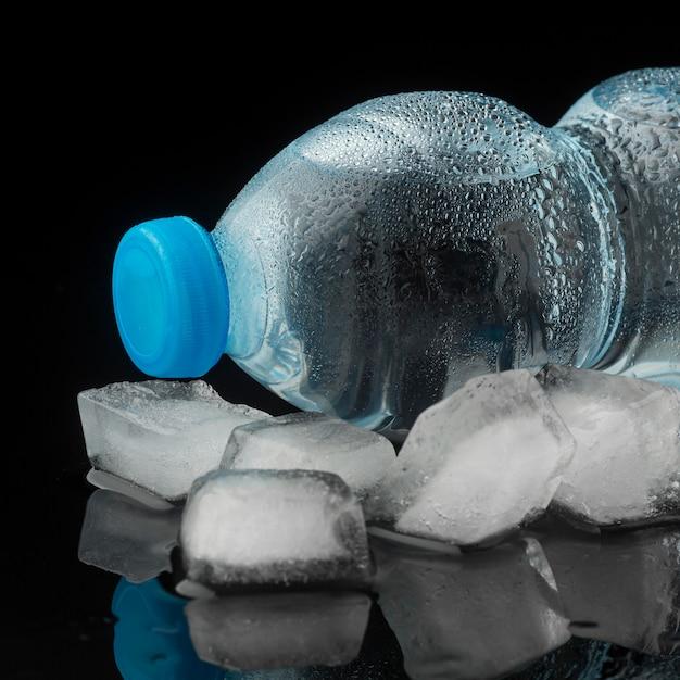 Cubos de gelo e garrafa de água vista frontal Foto gratuita