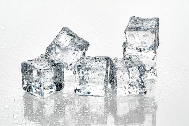 Cubos de gelo na parede branca. Foto Premium