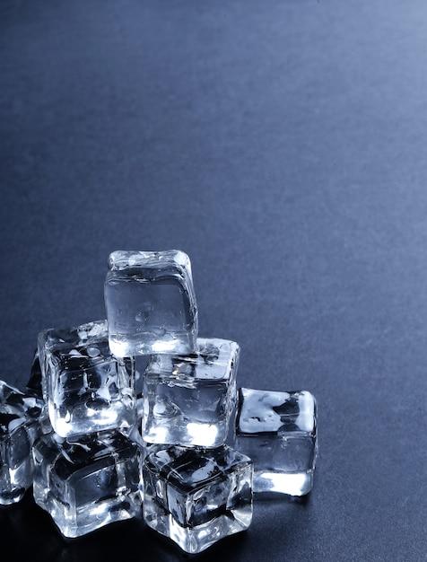 Cubos de gelo na superfície preta com copyspace Foto gratuita
