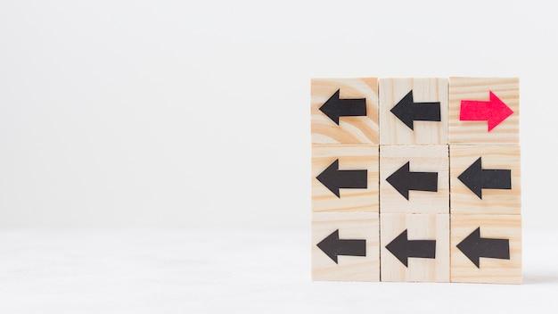 Cubos de madeira com conceito de originalidade de flechas Foto gratuita