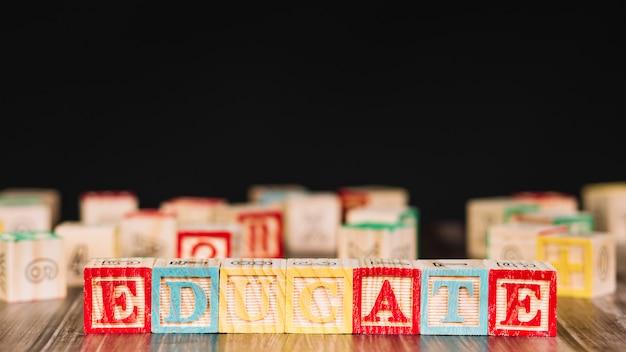 Cubos de madeira com inscrição de educar Foto gratuita