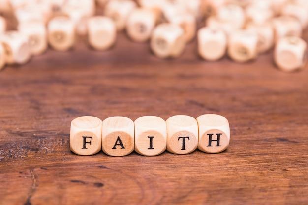 Cubos de madeira com palavra fé na mesa Foto gratuita