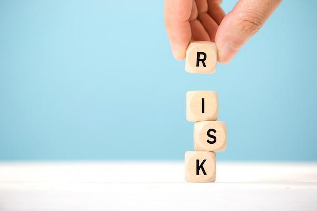Cubos de madeira da preensão da mão com palavra do risco. conceito de gerenciamento de risco. Foto Premium