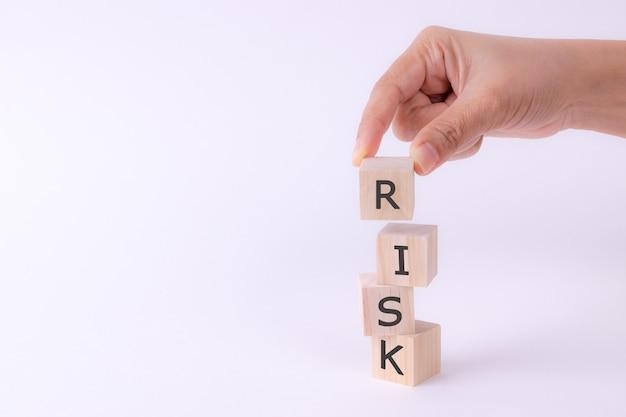 Cubos de madeira da preensão da mão com palavra do risco. Foto Premium