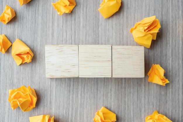Cubos de madeira vazios com papel desintegrado na mesa de madeira Foto Premium