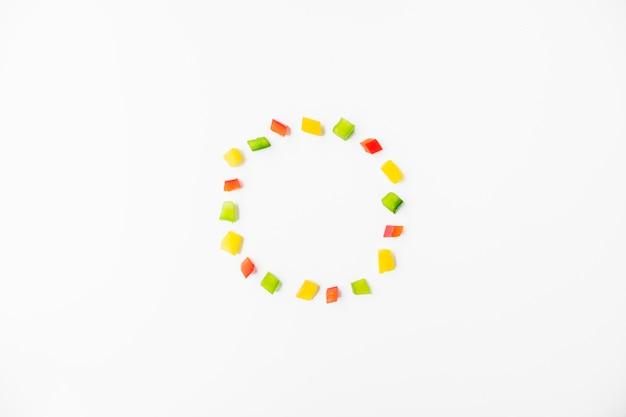 Cubos de pimentões coloridos, formando o quadro no fundo branco Foto gratuita