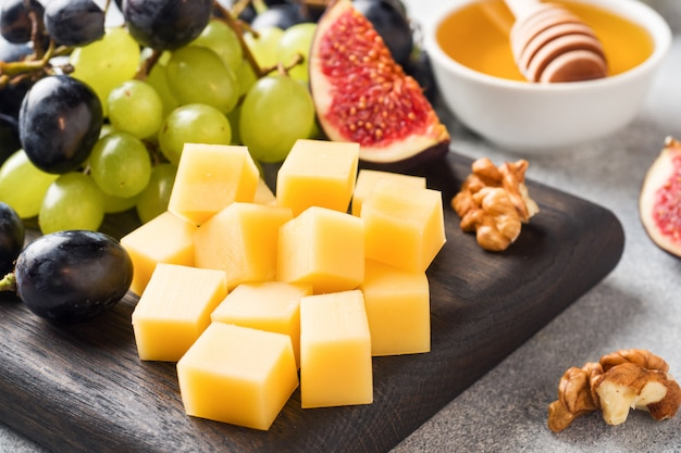 Cubos de queijo, uvas de figos de frutas frescas noz de mel na tábua de madeira. foco seletivo. fechar-se. Foto Premium