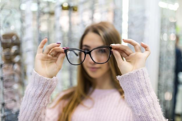 Cuidado, a jovem estudante está se preparando para o estudo da faculdade e experimenta novos óculos para seu visual perfeito em uma loja profissional Foto gratuita