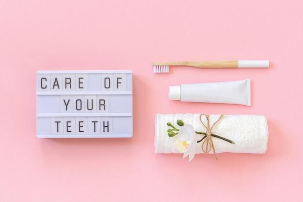 Cuidado de seus dentes texto na mesa de luz, escova de bambu natural eco-friendly para dentes, toalha, tubo de creme dental Foto Premium