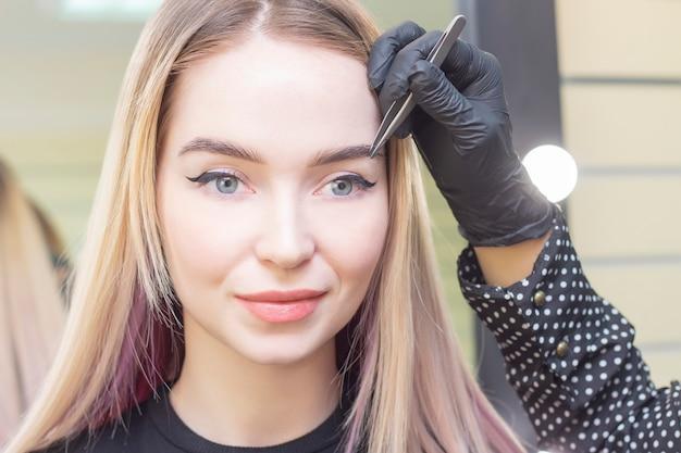 Cuidado de sobrancelha. pinça sobrancelhas com pinça. garota em um salão de beleza. menina loira Foto Premium