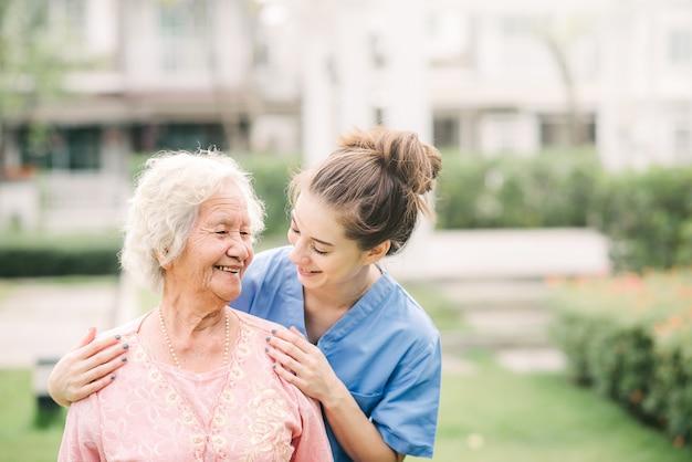 Cuidador com mulher idosa asiática ao ar livre Foto Premium