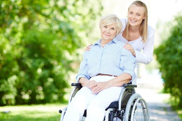 Cuidador empurra a mulher sênior na cadeira de rodas Foto gratuita
