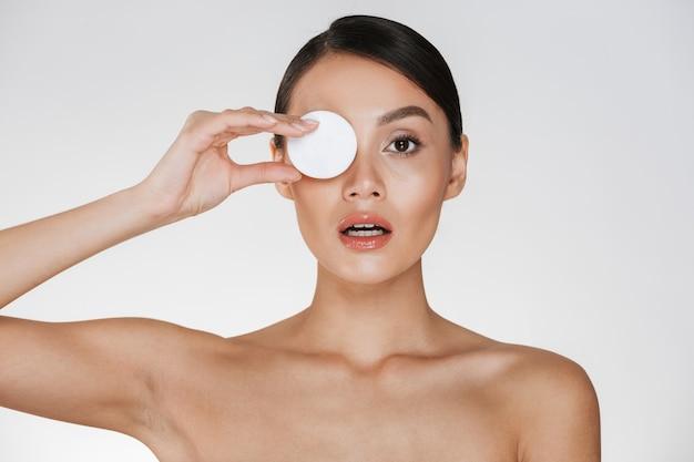 Cuidados com a pele e tratamento saudável da mulher colocando a almofada de algodão no olho enquanto remove cosméticos do rosto, isolado no branco Foto gratuita