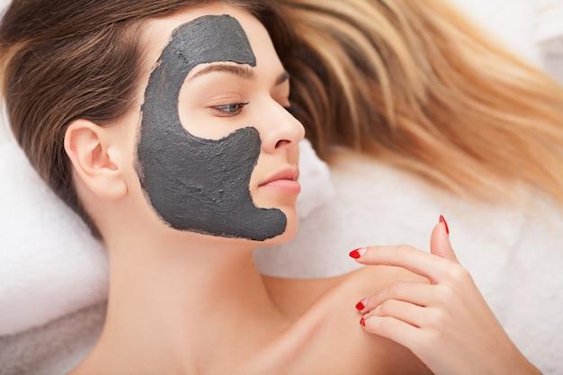 Cuidados com a pele facial. mulher bonita, ficando a máscara cosmética no salão Foto Premium