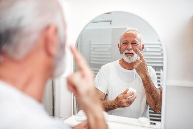 Cuidados com a pele. homem sênior que aplica o creme de cara no banheiro. Foto Premium