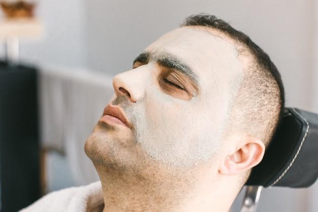 Cuidados com a pele masculina em um salão de beleza. aplicação de máscara de limpeza de argila no rosto de um homem Foto Premium