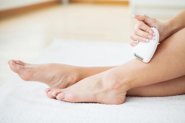 Cuidados com a pele. mulher, raspar, dela, pernas, em, banheiro Foto Premium
