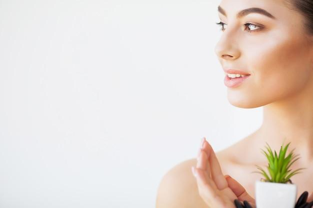 Cuidados com a pele. rosto de mulher beleza com pele saudável e planta verde Foto Premium