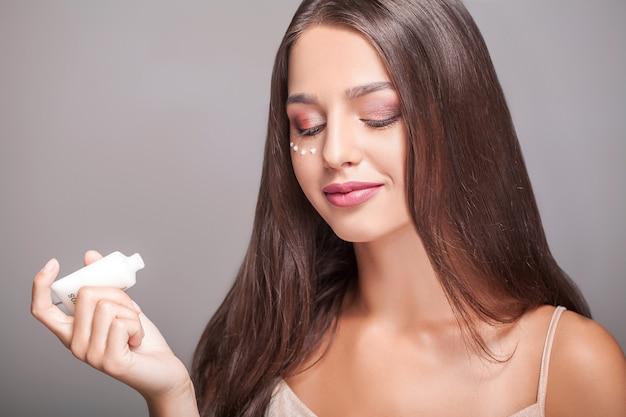 Cuidados com a pele rosto mulher. retrato da fêmea nova atrativa que aplica o creme sob os olhos e que guarda a garrafa. close up da menina de sorriso com composição natural e pele fresca. cosméticos de beleza. alta resolução Foto Premium