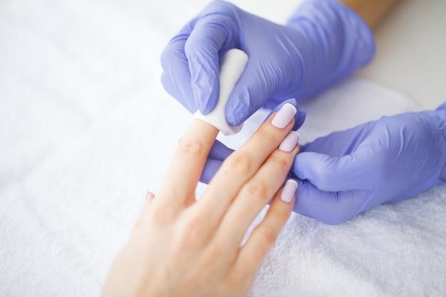 Cuidados com as mãos e unhas. o mestre dá serviços de manicure para o cliente. mãos de mulheres bonitas com manicure perfeita. beleza dia spa manicure Foto Premium