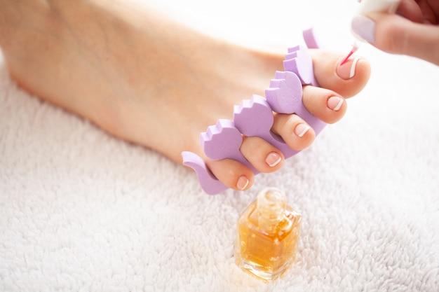 Cuidados com as mãos e unhas. os pés das mulheres bonitas com o pedicure no salão de beleza. o mestre aplicando na unha. spa manicure Foto Premium