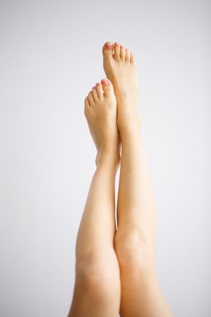 Cuidados com as mãos e unhas. pés das mulheres bonitas com pedicure perfeito. beleza dia spa manicure Foto Premium