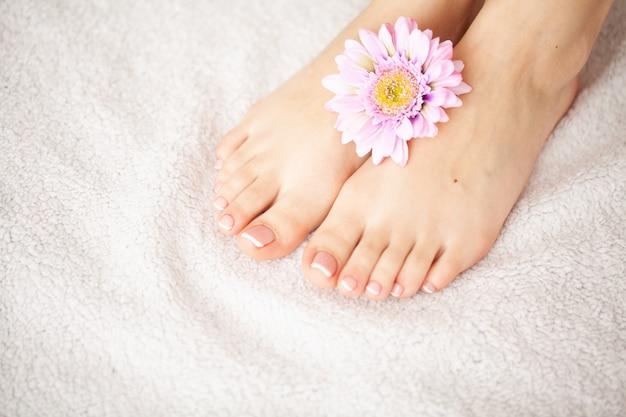 Cuidados com as mãos e unhas. pés e mãos das mulheres bonitas após o tratamento de mãos e o pedicure no salão de beleza. spa manicure Foto Premium