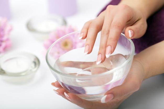 Cuidados com as unhas. close up das mãos bonitas da mulher que mostram os pregos perfeitos pintados com verniz para as unhas vermelho. mãos femininas perto conjunto de ferramentas de manicure profissional. tratamento de beleza. alta resolução Foto Premium