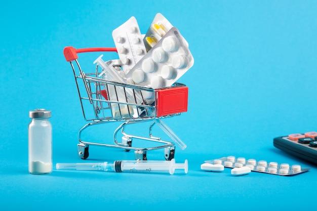 Cuidados de saúde caros. carrinho de compras com remédios e calculadora Foto Premium