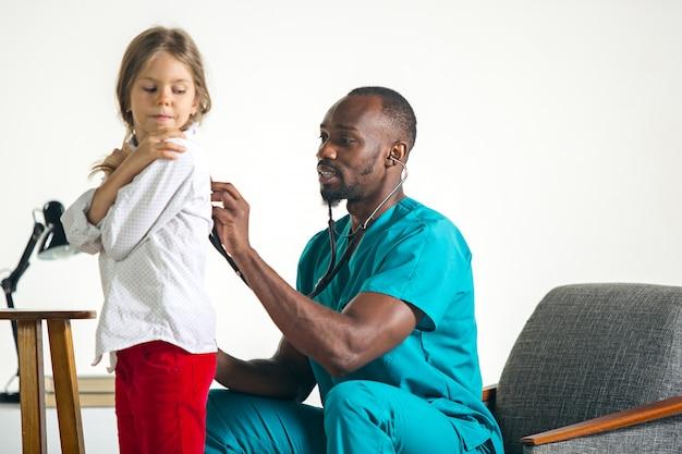 Cuidados de saúde e conceito médico - médico com estetoscópio, ouvindo o peito de criança no hospital Foto gratuita