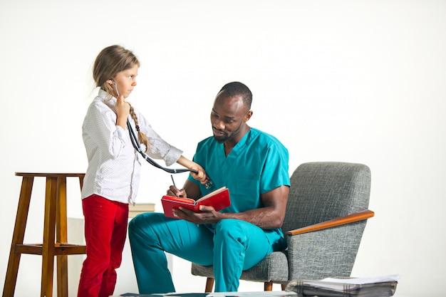 Cuidados de saúde e conceito médico - médico e menina com estetoscópio no hospital Foto gratuita