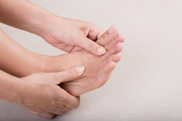 Cuidados de saúde e médicos. mulher massageando seu pé doloroso. Foto Premium