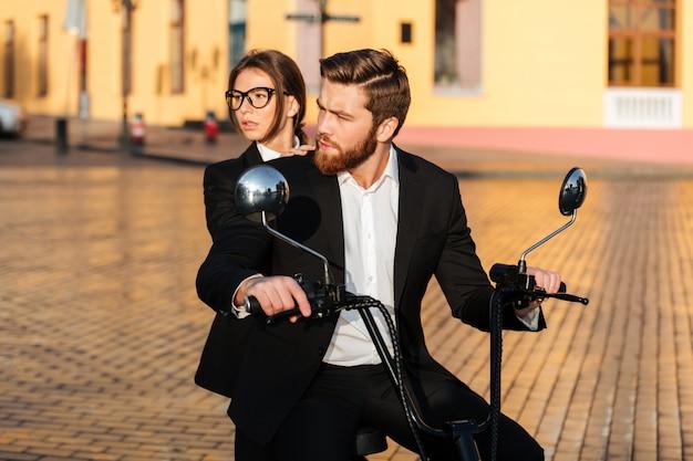 Cuidadoso casal de negócios monta na moto moderna no parque Foto gratuita