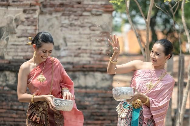 Cultura da tailândia. meninas tailandesas e mulheres tailandesas que jogam espirrando a água durante com o traje tradicional tailandês no templo do festival de songkran do festival de ayutthaya tailândia. Foto Premium