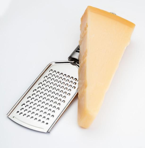 Cunha de queijo parmesão ou grana com ralador. isolado Foto Premium