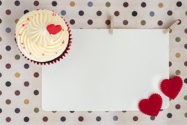 Cupcake com dois corações vermelhos sobre papel em branco Foto gratuita