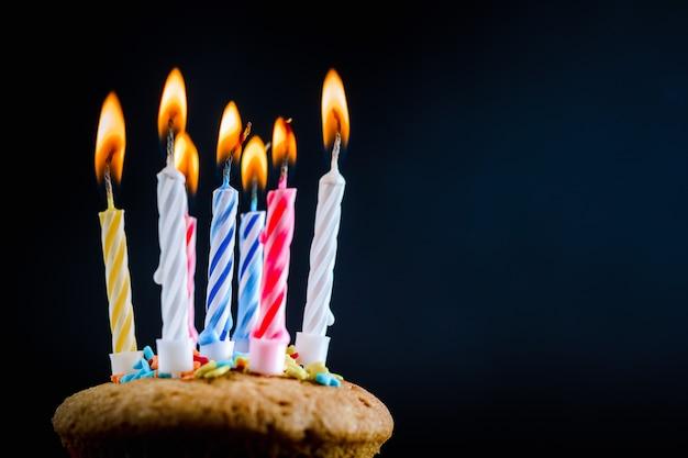 Cupcake com queima de velas festivas em um fundo preto Foto Premium
