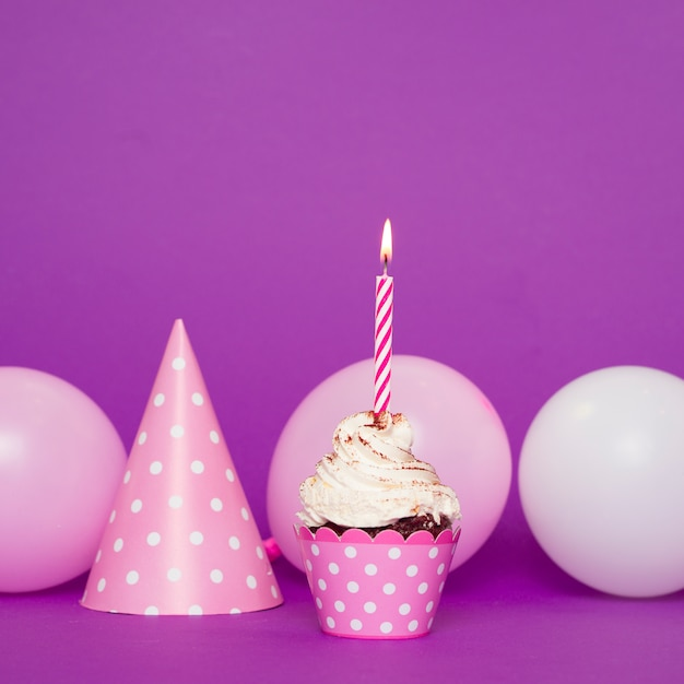 Cupcake com vela acesa ao lado do chapéu Foto gratuita