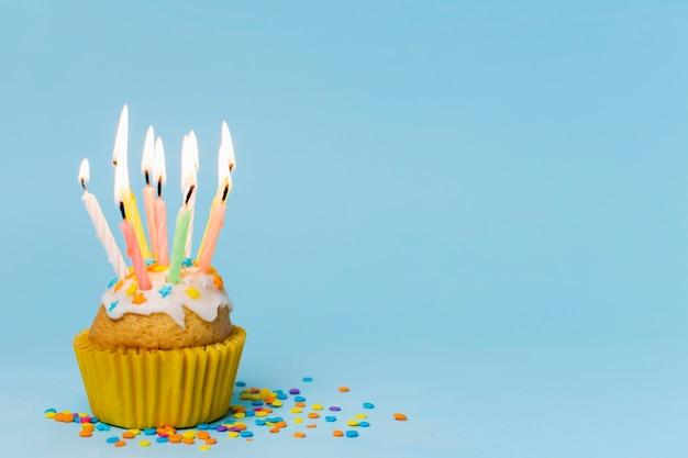 Cupcake com velas acesas sobre fundo azul, com espaço de cópia Foto gratuita