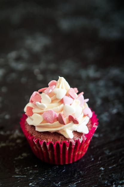 Cupcake comemorativo para dia dos namorados na mesa de madeira preta com corações. Foto Premium