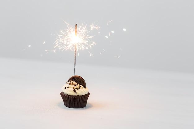 Cupcake de aniversário com brilho sobre parede branca com espaço de cópia Foto Premium