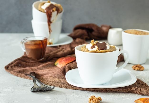 Cupcake de cenoura ou abóbora com chantilly, molho de caramelo e nozes em uma caneca de cerâmica branca. Foto Premium