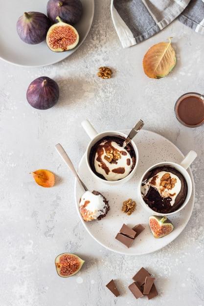 Cupcake de chocolate com queijo creme ou ricota com molho de caramelo em uma caneca de cerâmica branca. comida de outono ou inverno de conforto. Foto Premium