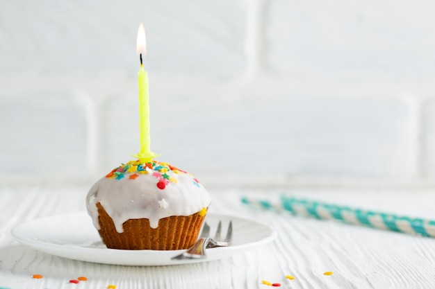 Cupcake glazed com vela acesa Foto gratuita