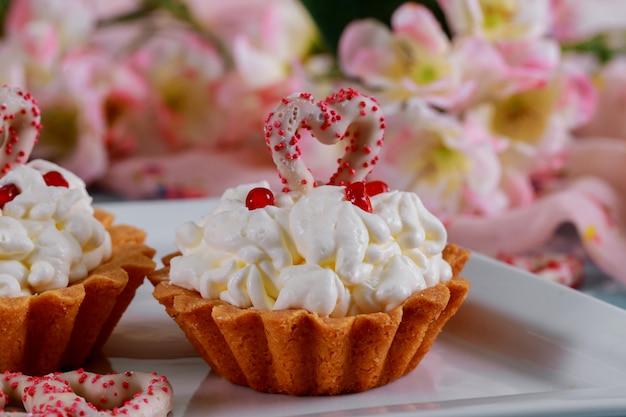 Cupcakes caseiros dos namorados com corações de açúcar vermelho e fundo de flores cor de rosa Foto Premium