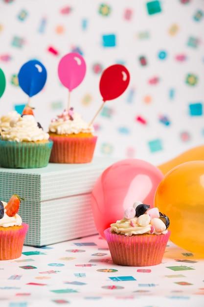 Cupcakes com balões na mesa Foto gratuita
