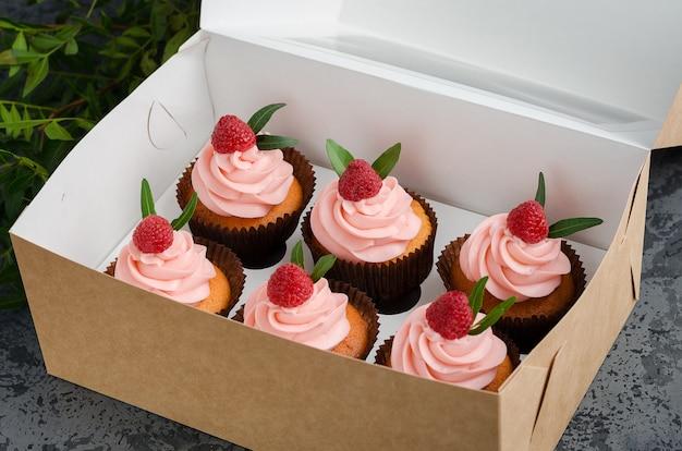 Cupcakes com creme de framboesa, decorado com framboesas em cima no embrulho. Foto Premium